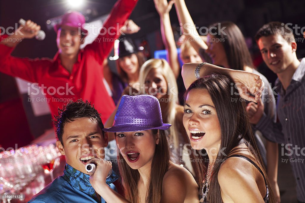 Friends singing at the disco club. royalty-free stock photo