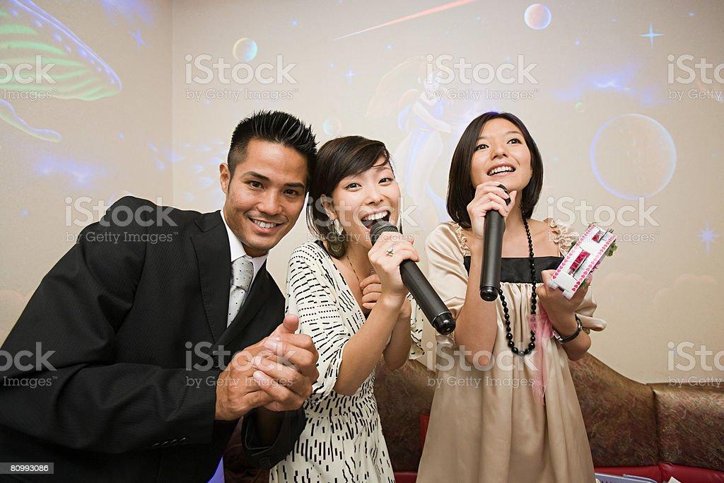 Friends singing karaoke stock photo