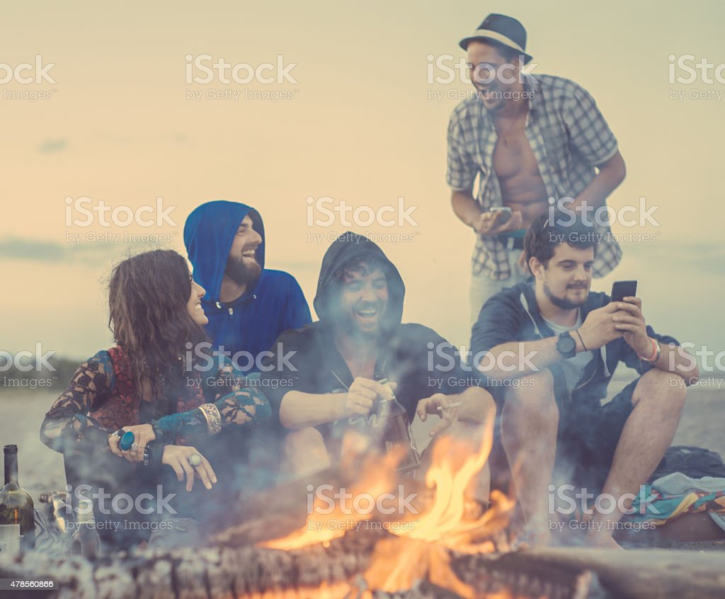 friends sitting around a camp fire stock photo