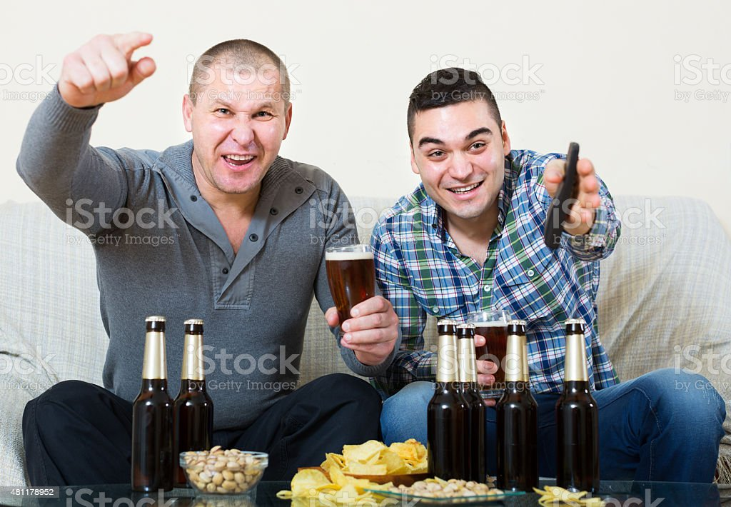 friends sitting at table with beer stock photo
