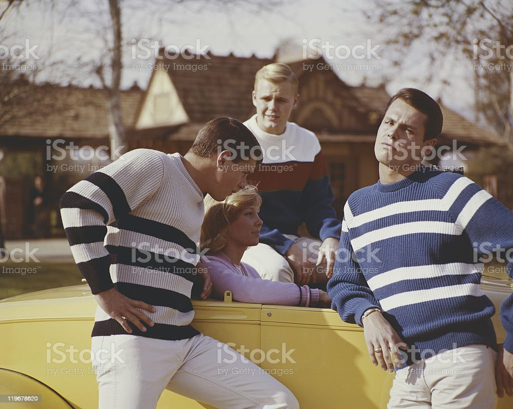 Friends sitting in car and standing beside it stock photo
