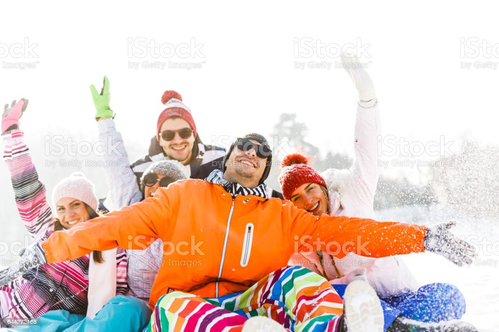 Friends sitting in snow with arms outstretched stock photo