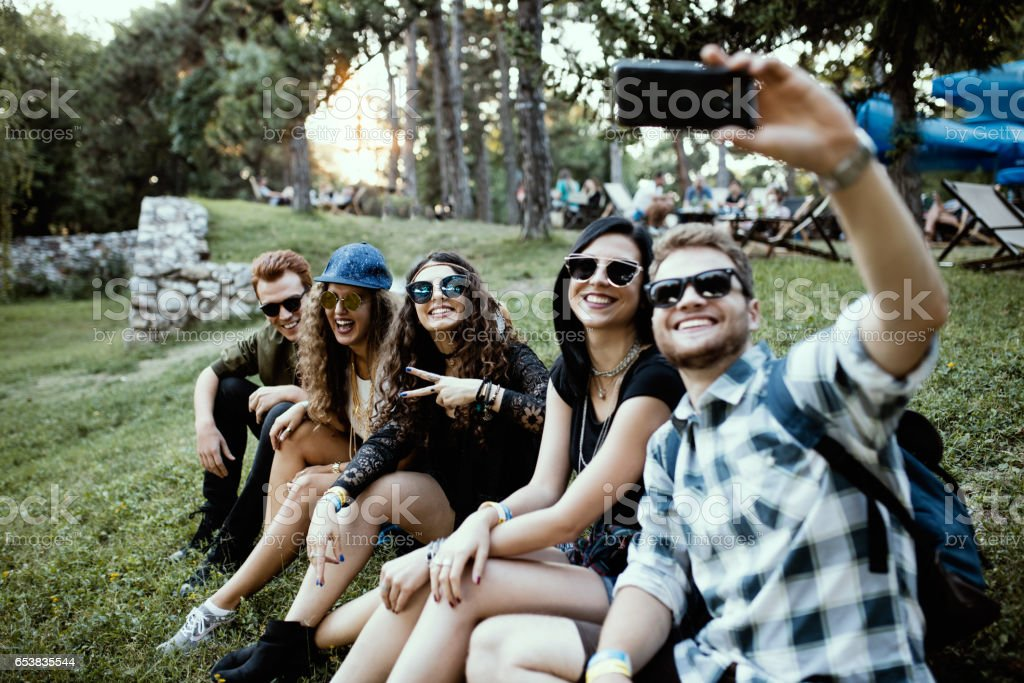 Friends sitting in the grass, having a laugh and taking selfie stock photo