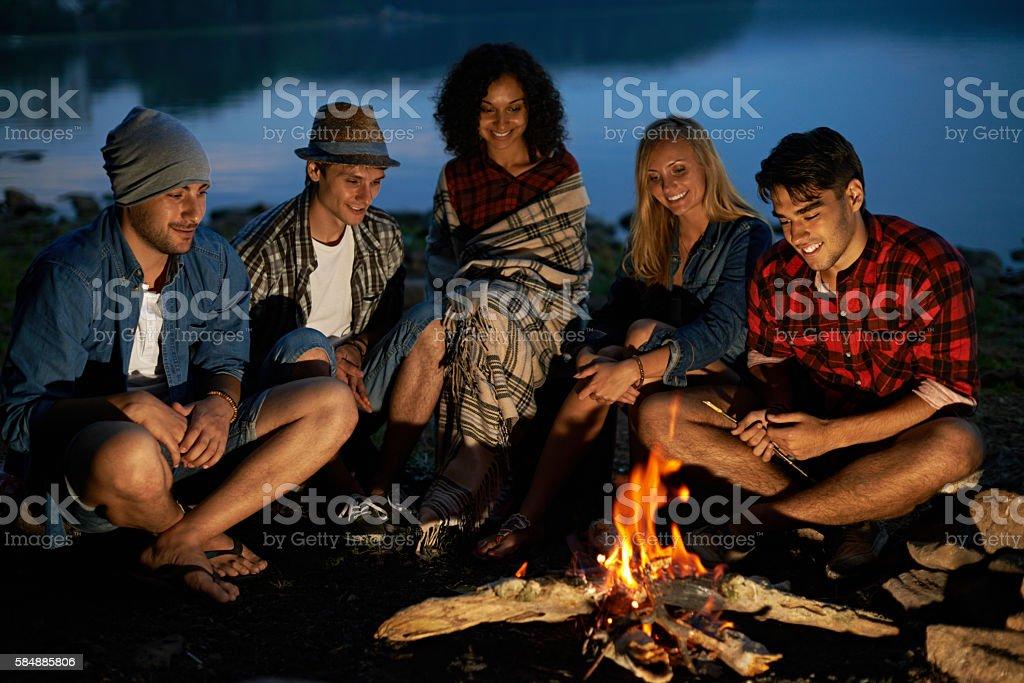 Friends sitting near campfire stock photo