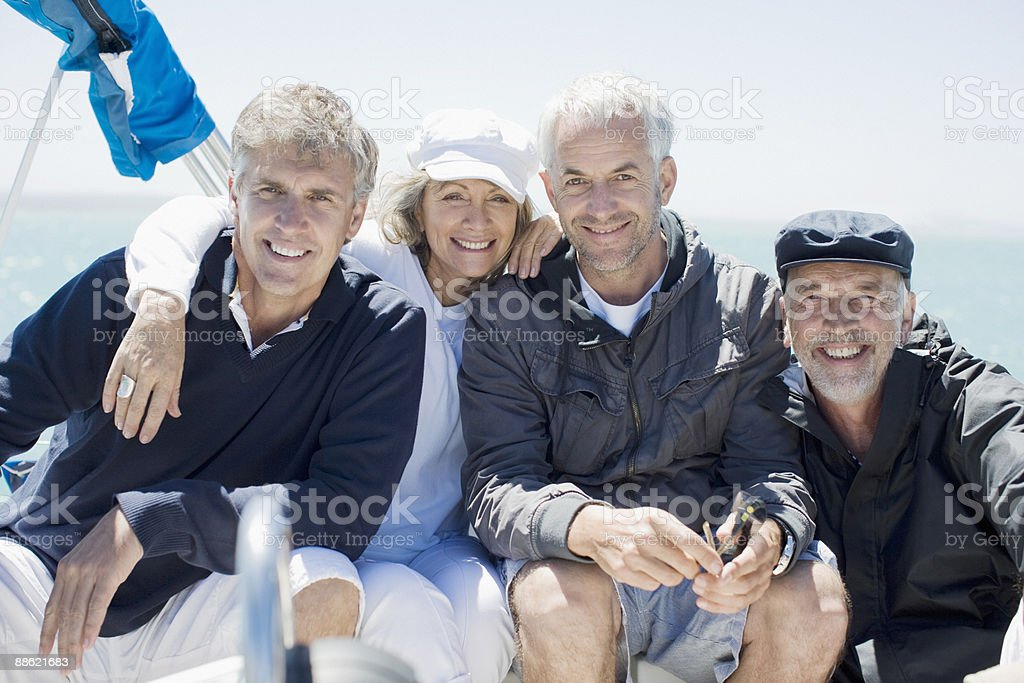 Friends sitting on deck of boat together royalty-free stock photo