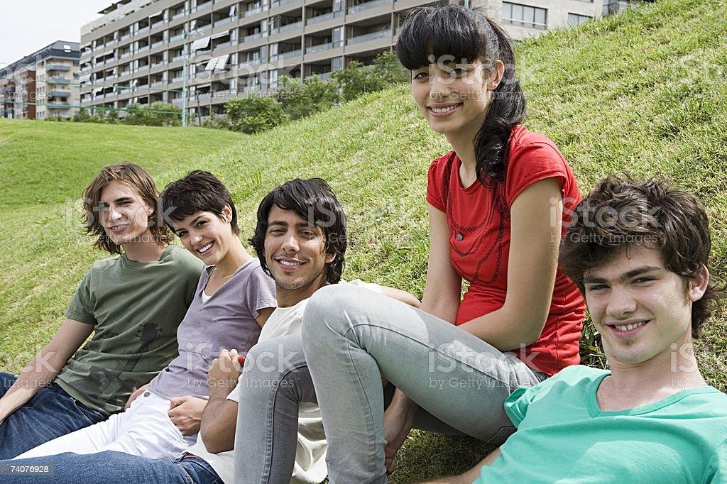 Friends sitting on grass verge stock photo