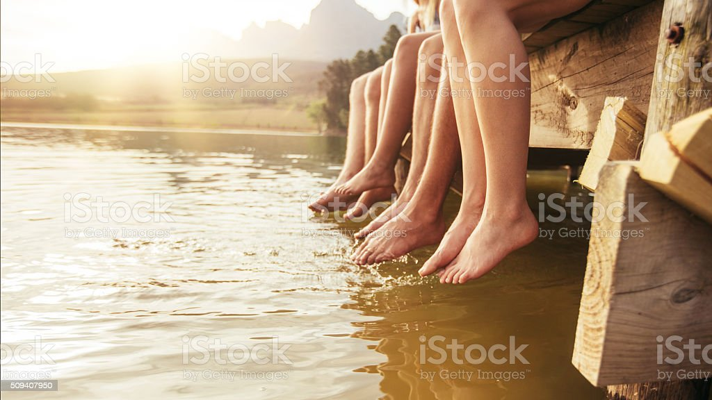 Friends sitting on jetting with their legs hanging down stock photo