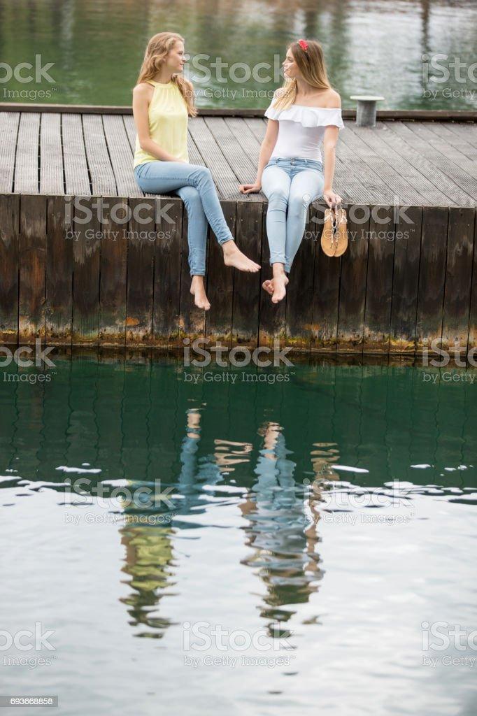 Friends sitting on jetty stock photo