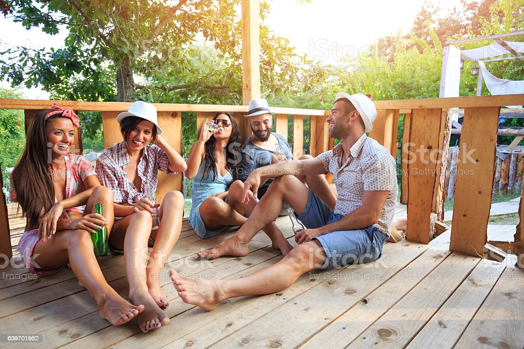 Friends sitting on veranda and drinking beer stock photo