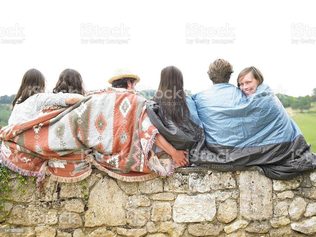 Friends Sitting Together on Stone Wall royalty-free stock photo