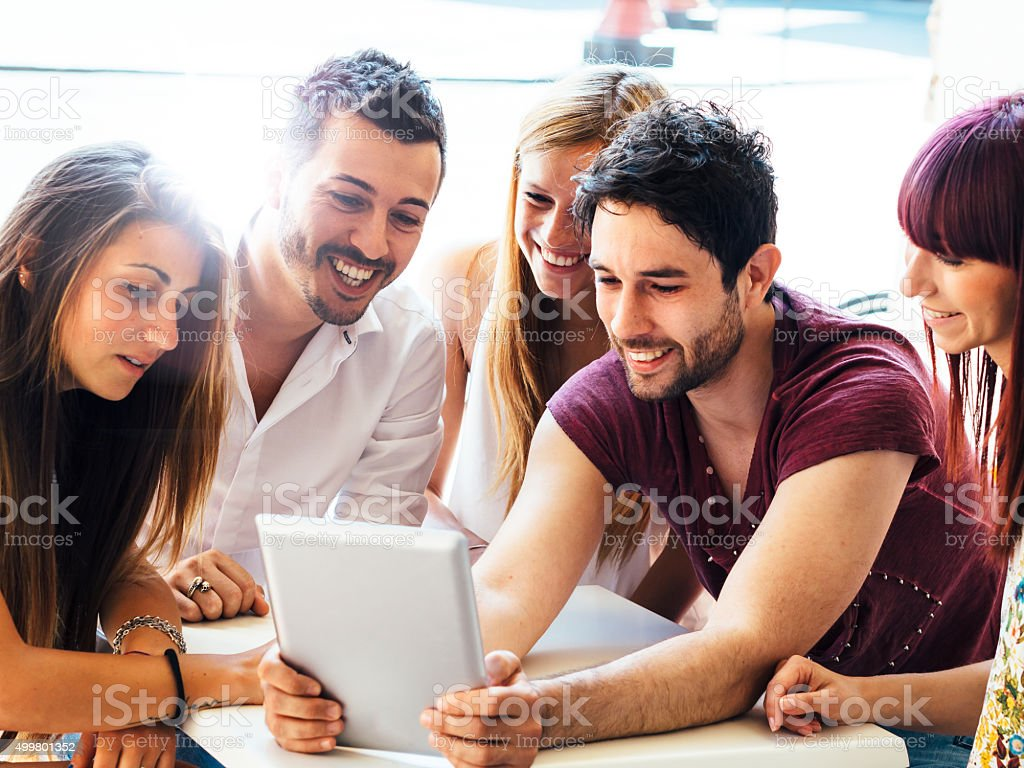 Friends Sitting Together Using Tablet stock photo