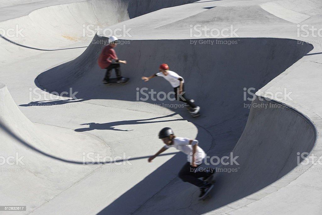 Friends Skateboarding In Park stock photo