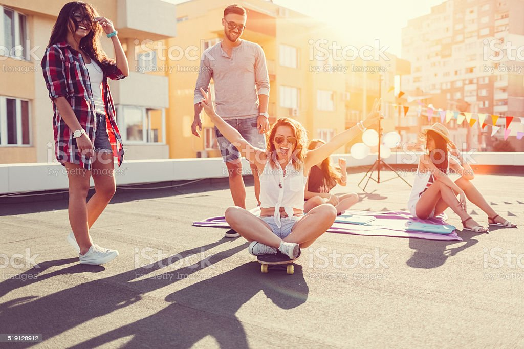 Friends skateboarding on the rooftop stock photo