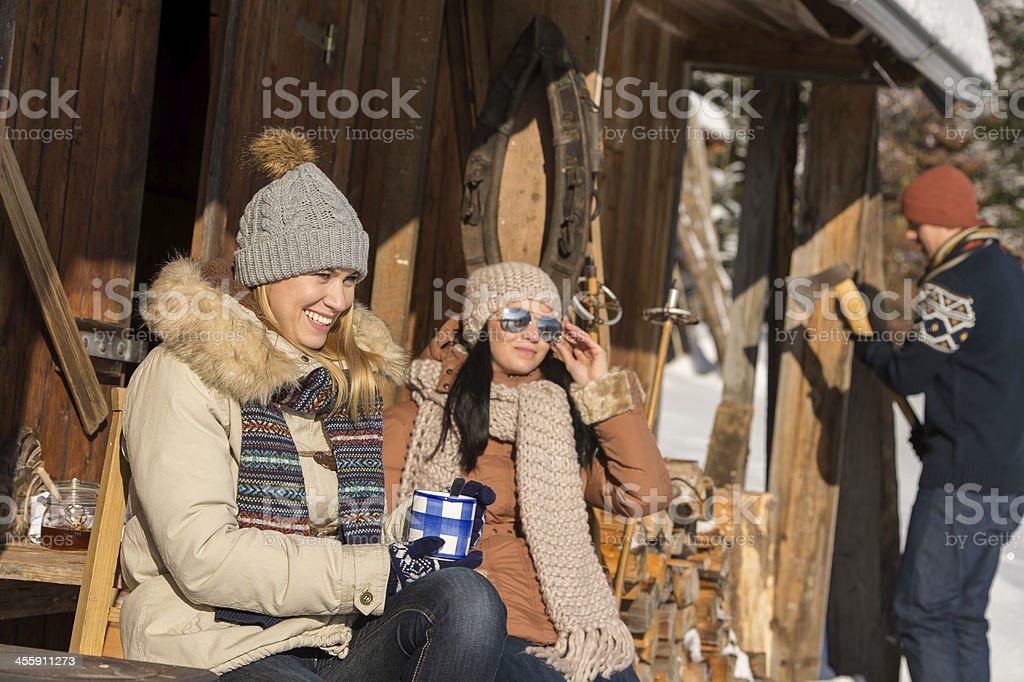 Friends spending winter holiday on mountain cottage snow stock photo