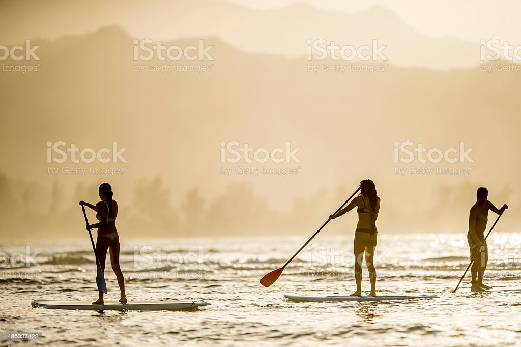 Friends Stand Up Paddle Boarding at Dusk stock photo