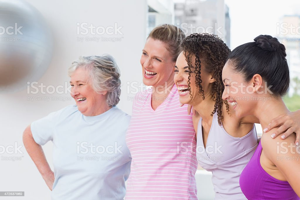 Friends standing arms around in fitness studio stock photo