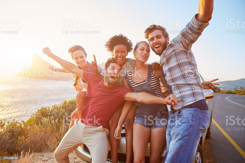 Friends standing by a car next to a coastal road at sunset stock photo