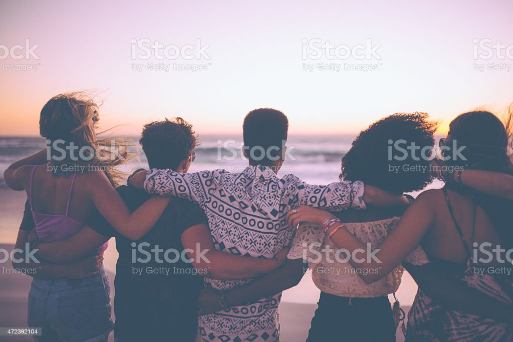 Friends standing in a row watching the ocean at sunset stock photo