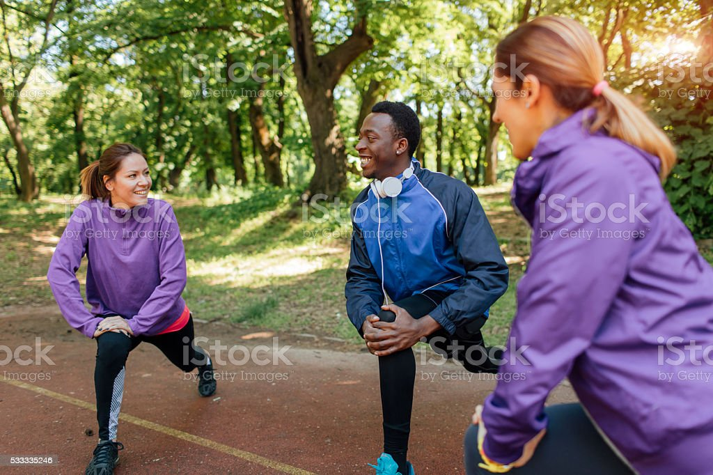 Friends stretching after jogging. stock photo