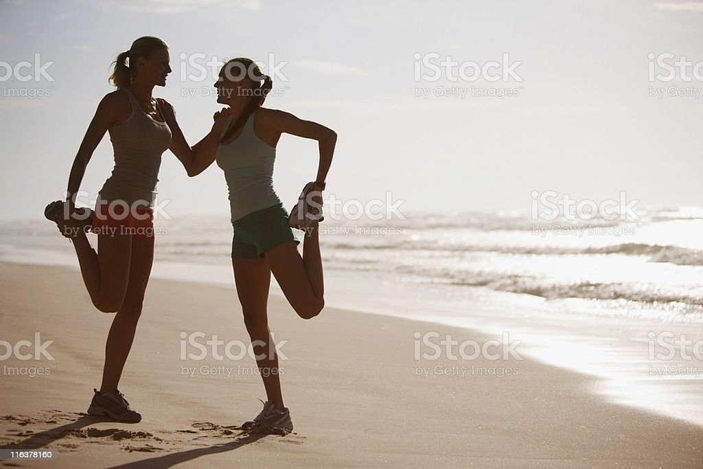 Friends stretching on beach royalty-free stock photo