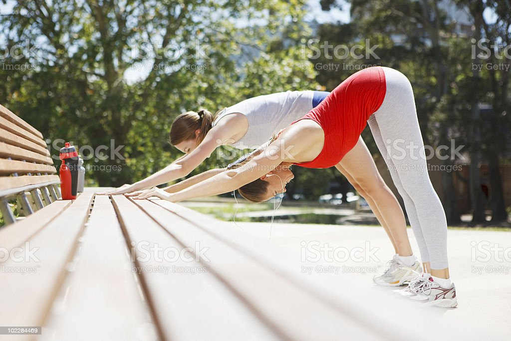 Friends stretching on park bench royalty-free stock photo
