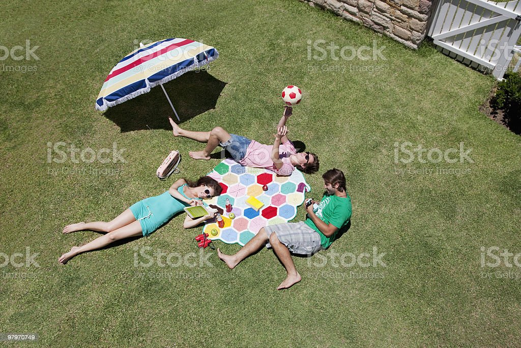 Friends sunbathing and relaxing on sunny grass royalty-free stock photo