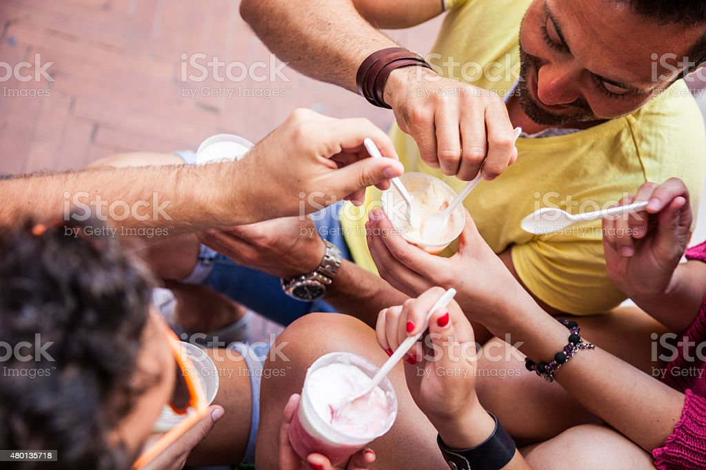 Friends taking a break outdoors eating an ice cream stock photo