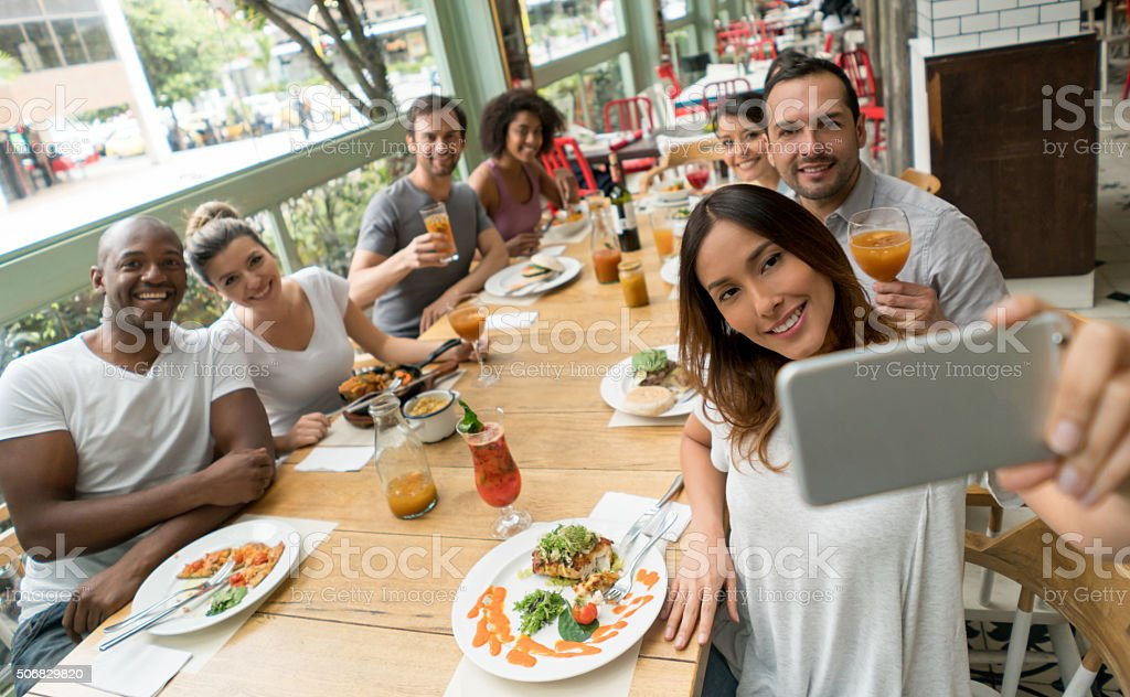 Friends taking a selfie at a restaurant stock photo