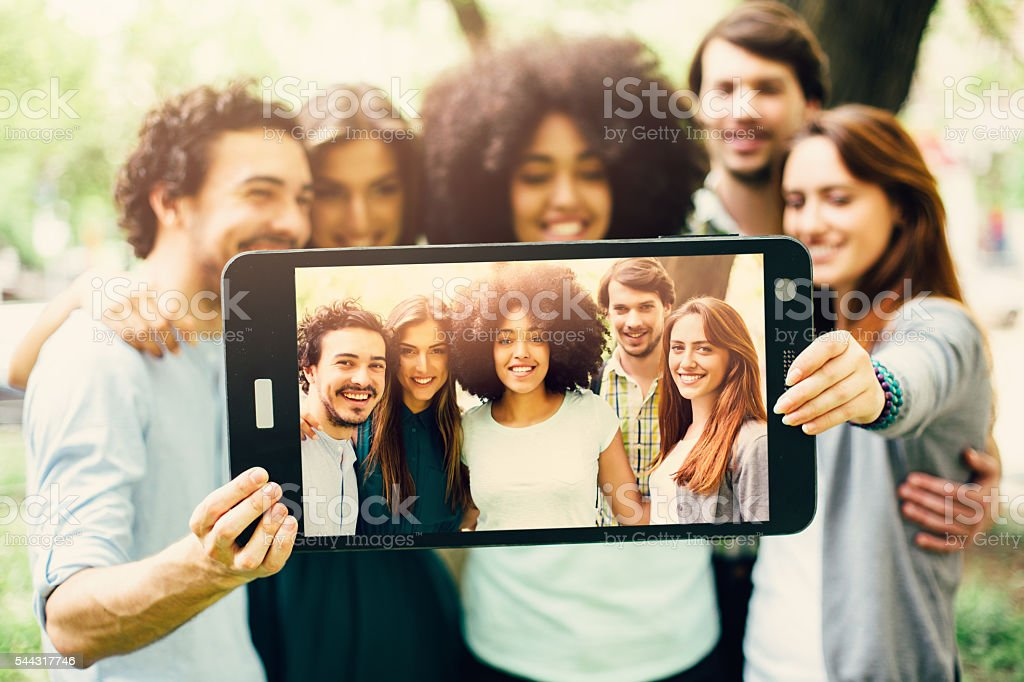 Friends taking a selfie with a large smart phone stock photo