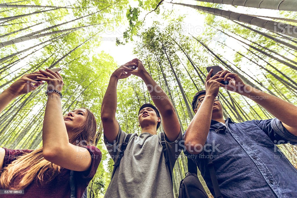 Friends taking bamboo forest pictures at Arashiyama, Kyoto, Japan stock photo