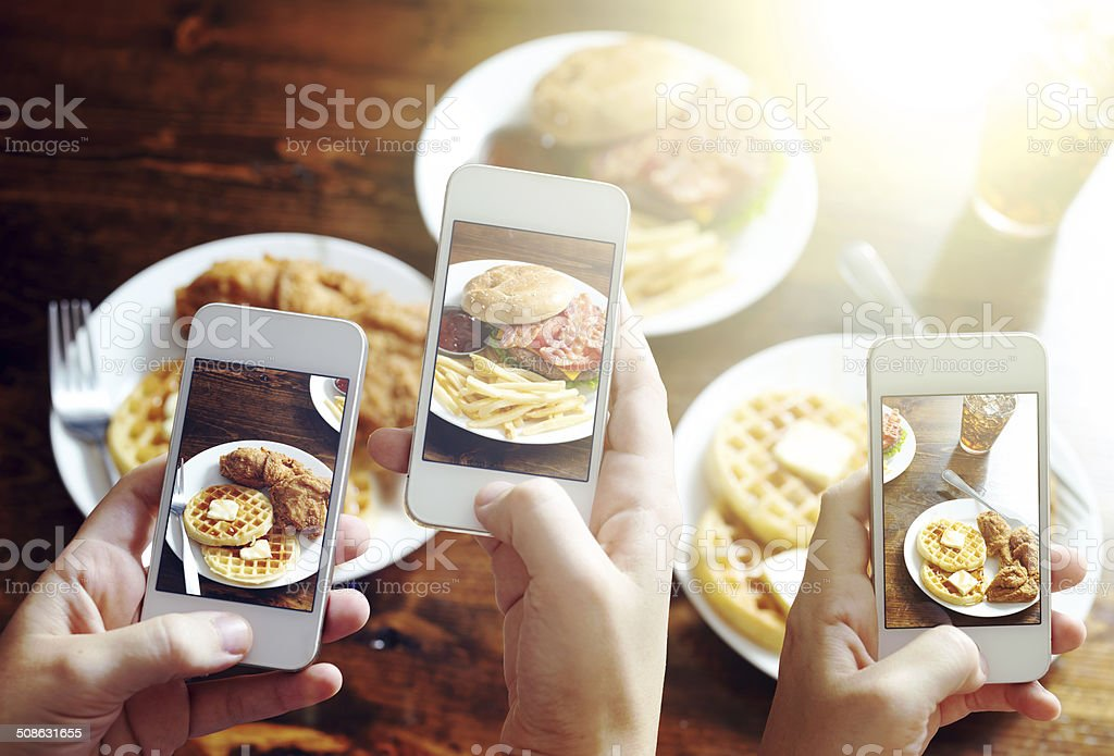 friends taking photos of food with smart phones stock photo