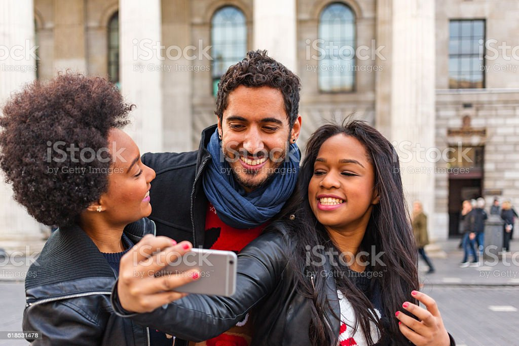 Friends Taking Selfie While Christmas Shopping in Ugly Festive Sweaters stock photo