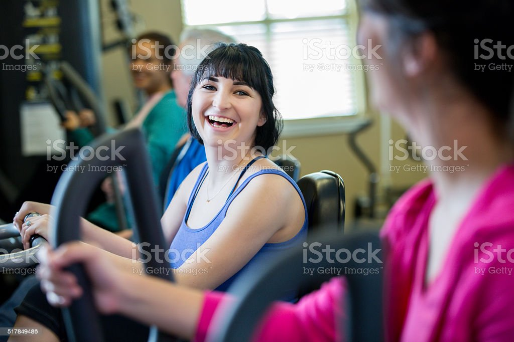 Friends talk as they exercise on stationary bicycle stock photo