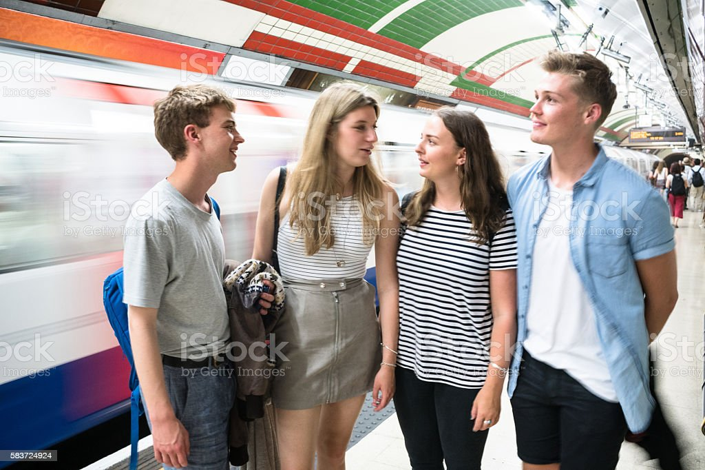 friends talking and waiting the train on a subway station stock photo