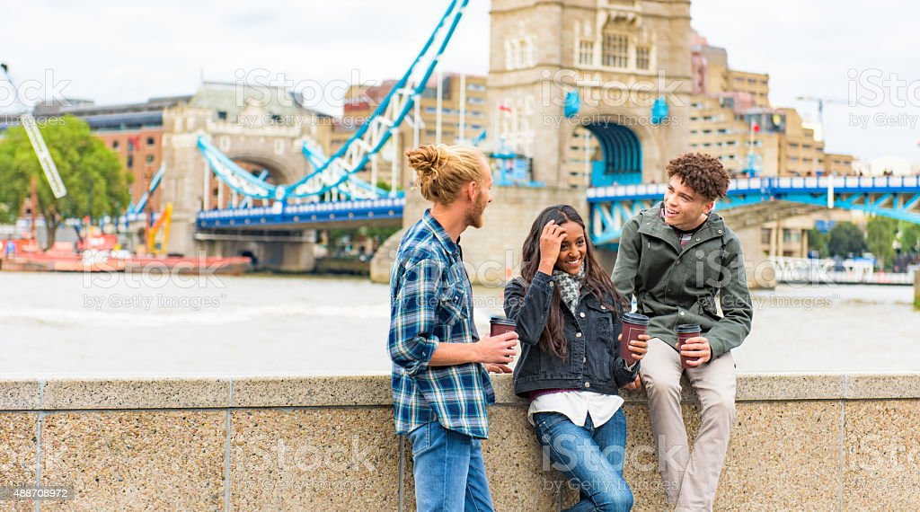 Friends talking by Tower Bridge London stock photo