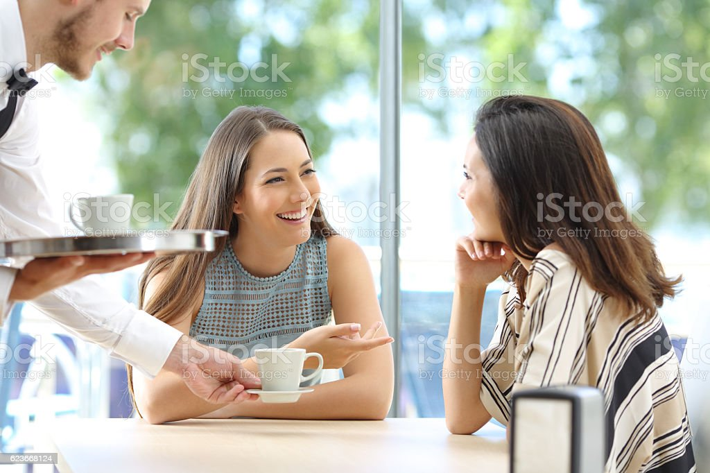 Friends talking in a bar with waiter serving stock photo