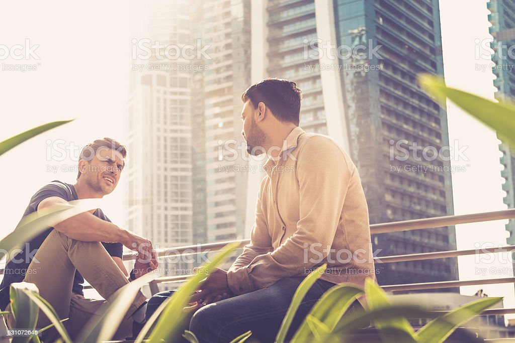 Friends talking outside their office building stock photo