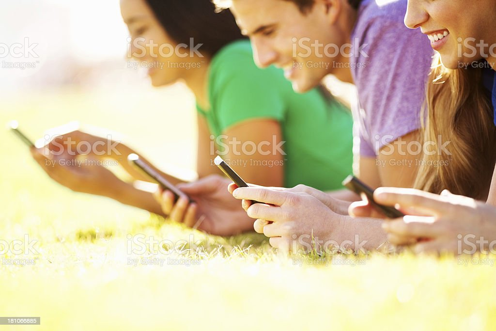 Friends Text Messaging Through Smart Phone While Lying On Grass royalty-free stock photo