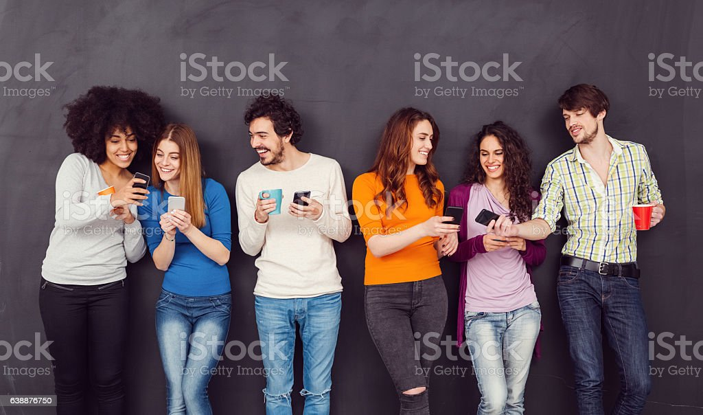 Friends texting on smartphones stock photo