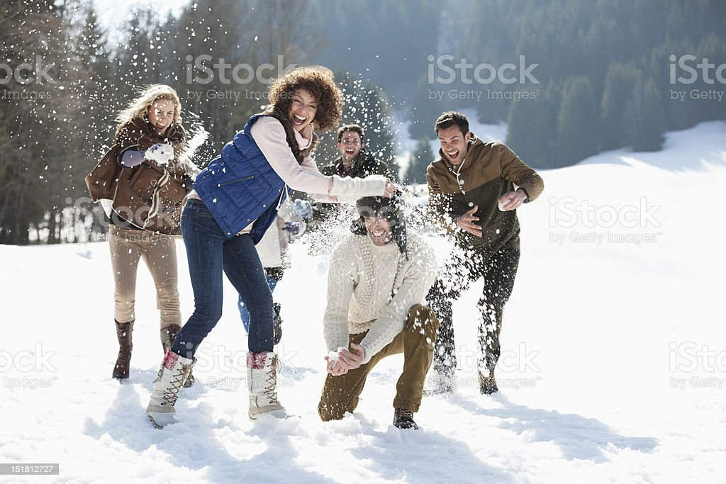 Friends throwing snowballs in field stock photo