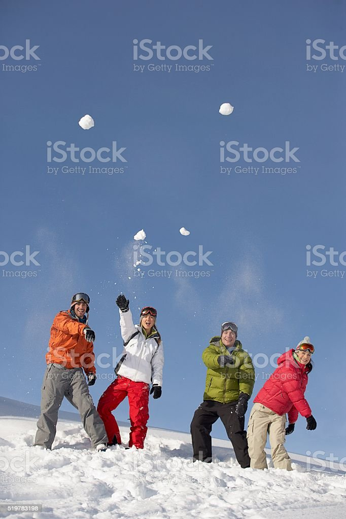 Friends throwing snowballs stock photo