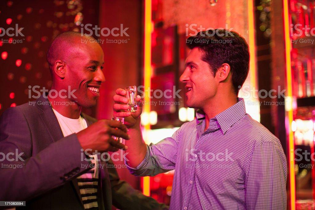 Friends toasting glasses in nightclub stock photo