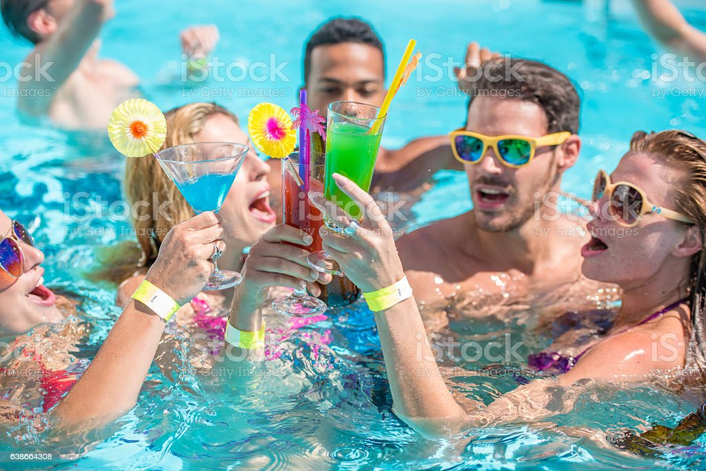 Friends toasting in pool stock photo