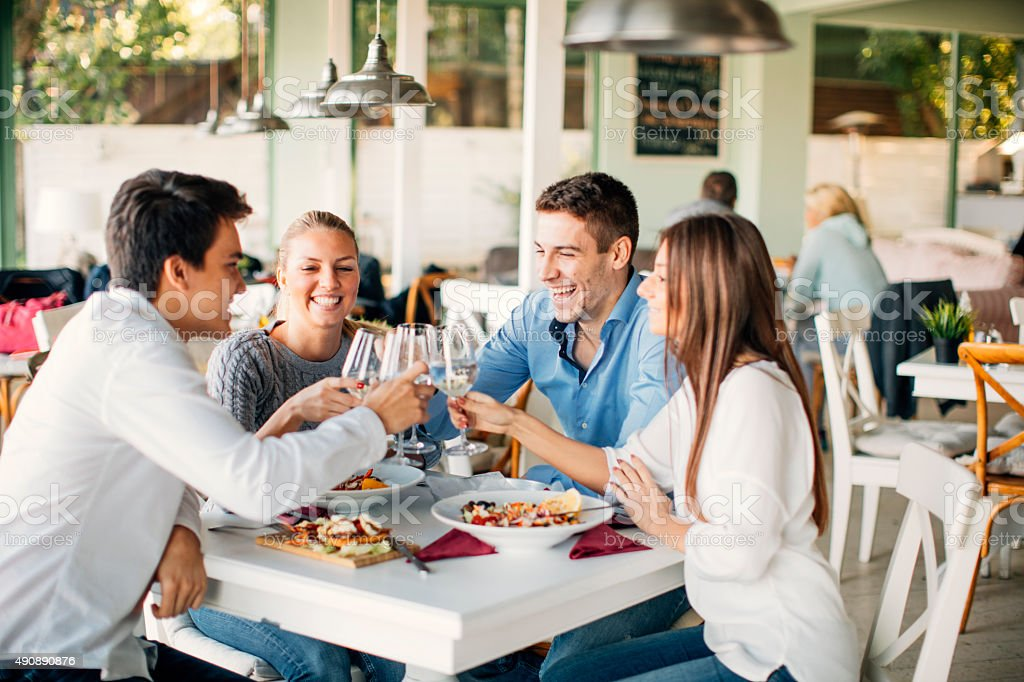 Friends Toasting In Restaurant. stock photo
