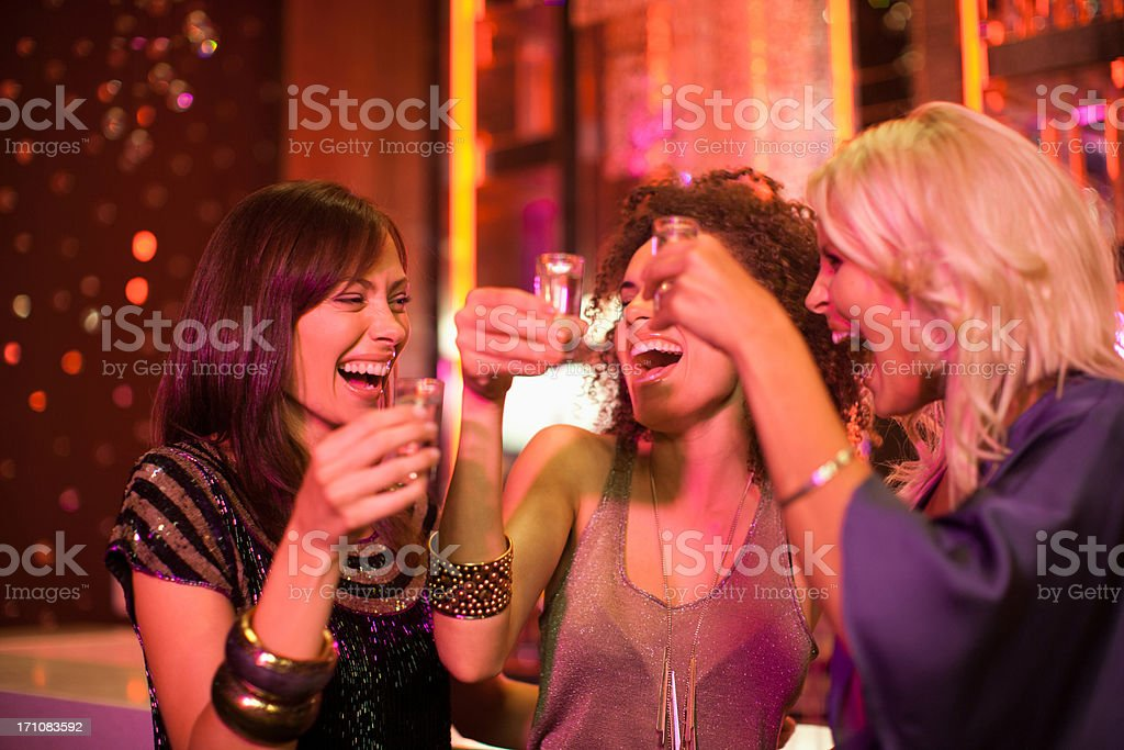 Friends toasting shot glasses in nightclub stock photo