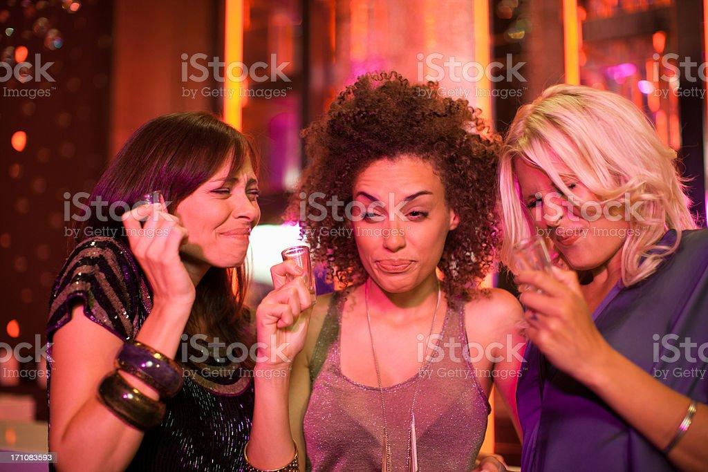 Friends toasting shot glasses in nightclub stock photo