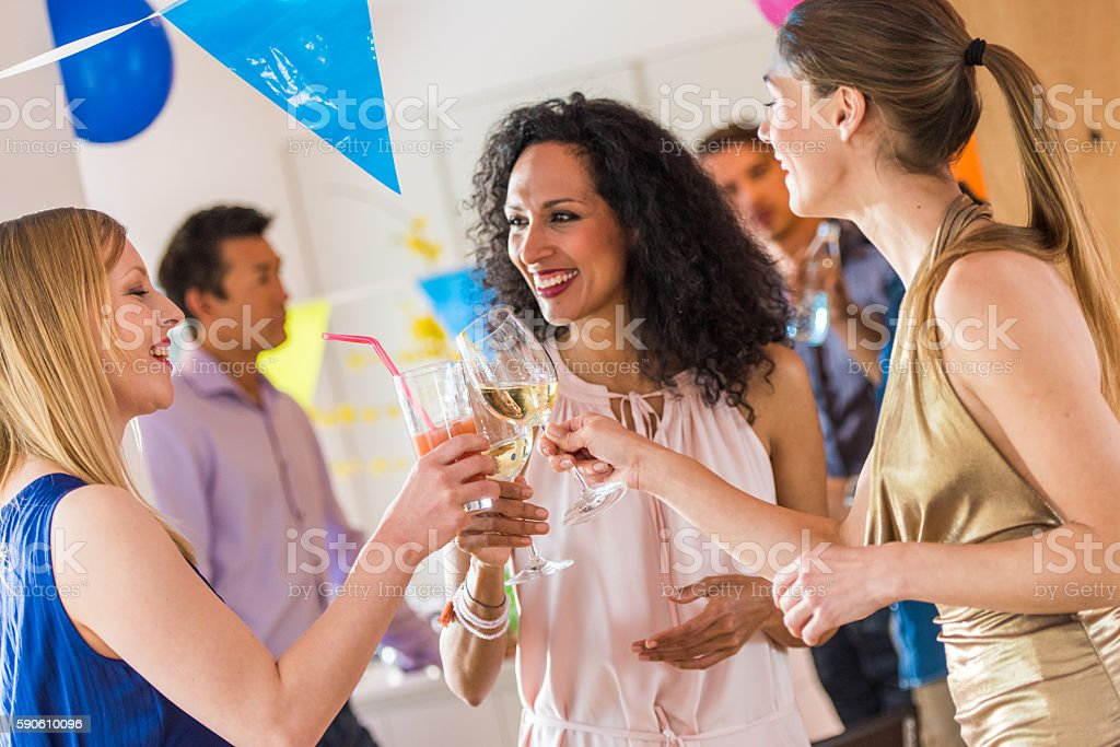 Friends toasting wine at party stock photo