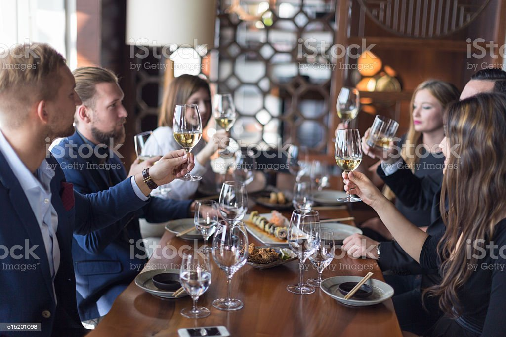 Friends toasting wine in restaurant stock photo