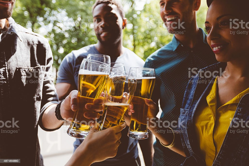 Friends toasting with beer outdoors stock photo
