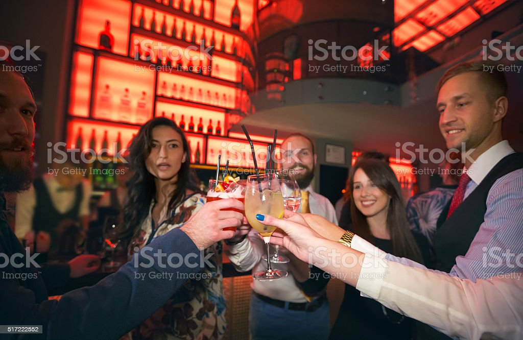 Friends toasting with cocktails in bar stock photo